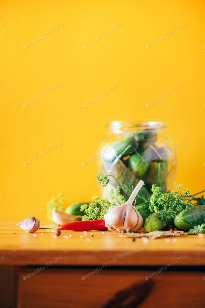 Ingredients, spices and herbs for canning cucumbers on yellow background. Copy space. Dill flowers