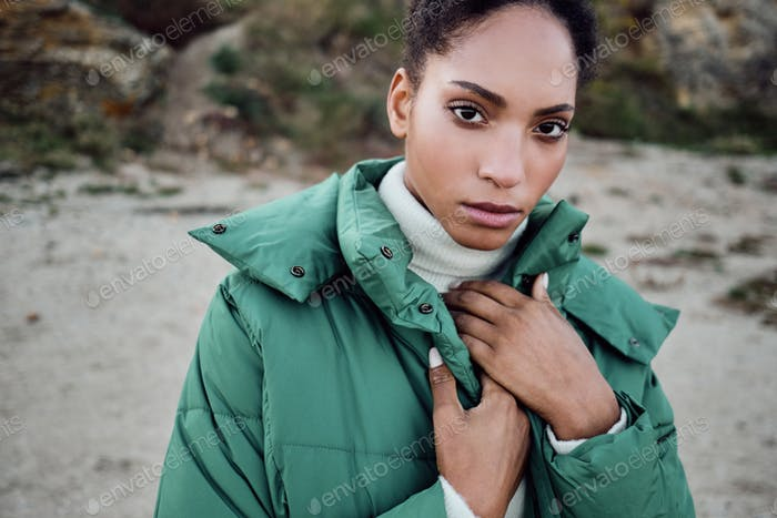 Beautiful serious African American girl in down jacket intently looking in camera posing outdoor