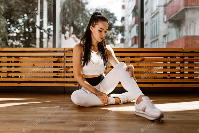 Slim dark-haired girl dressed in white sports clothes sits on the floor near the window in the gym