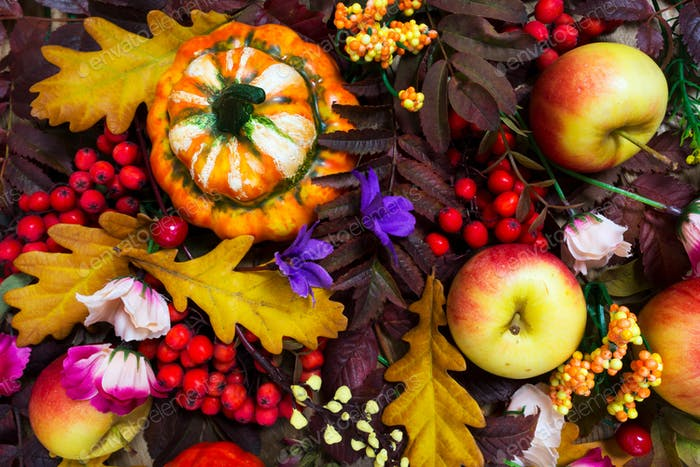 Thanksgiving arrangement with decorative pumpkin, apples, fall r