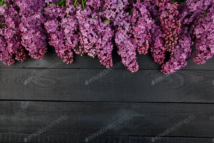 Beautiful lilac flower bouquet on black wooden background.