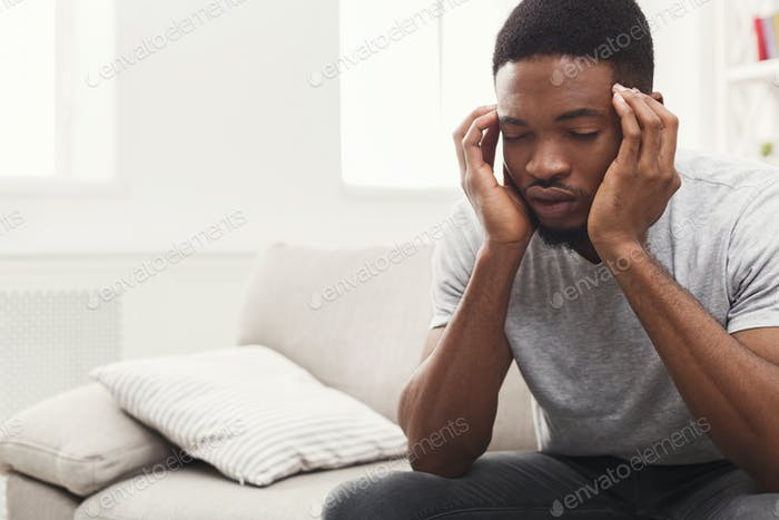 Young african-american man having headache at home