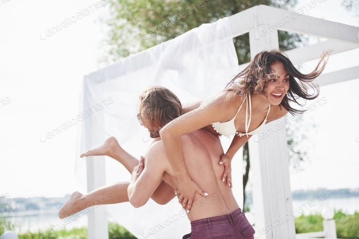 Beautiful young people are fond of it. A man holds a woman on his shoulders, they are playful and
