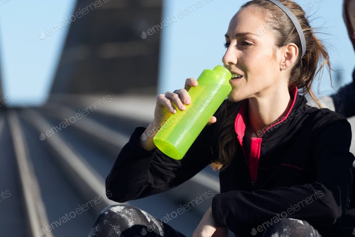 Fit and sporty young woman drinking water.