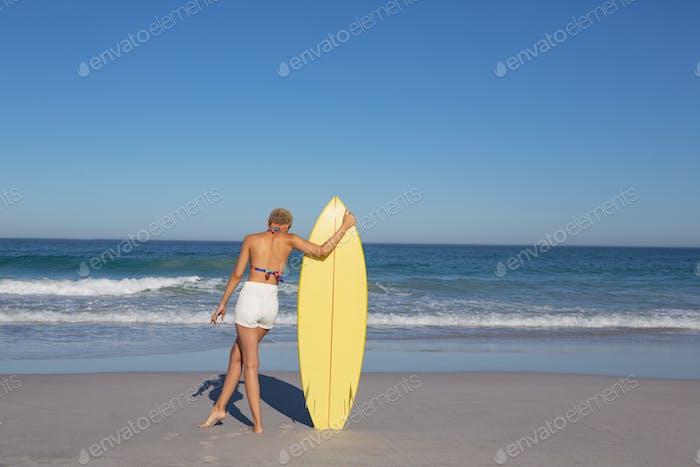 Rückansicht von African American Frau im Bikini stehend mit Surfbrett am Strand in der Sonne