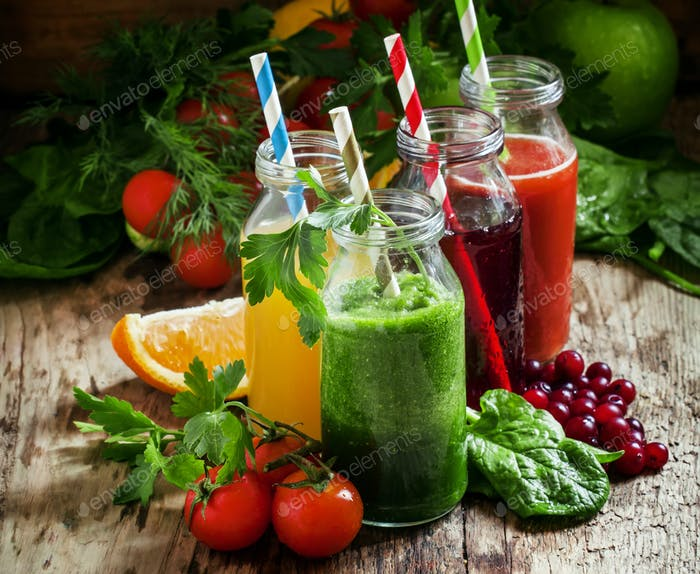 Mix of healthy fruit and vegetable juices in small bottles with colored striped straw