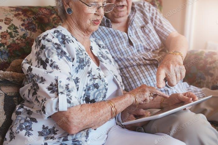Пенсионер пара дома с помощью компьютера с сенсорным экраном
