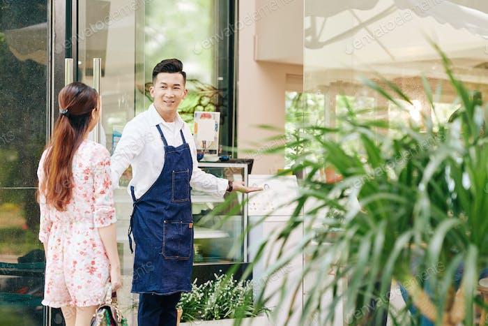Waiter opening door for client