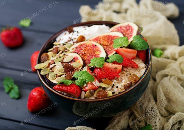 Köstliche und gesunde Haferflocken mit Feigen, Samen, Erdbeere und Joghurt.