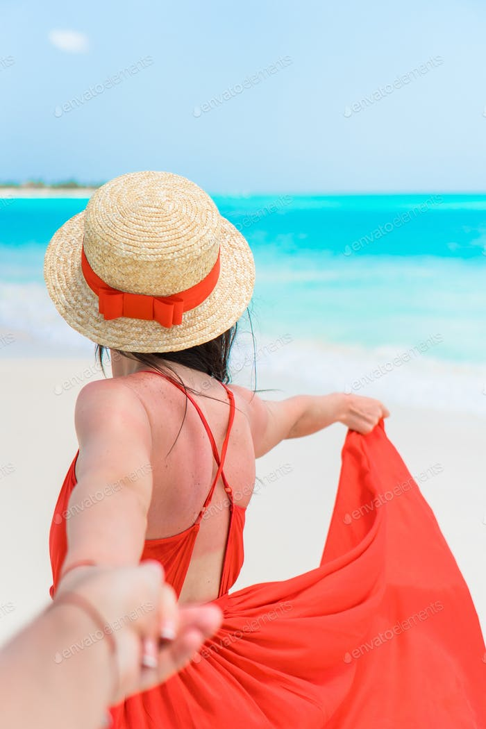 Young beautiful woman in hat on tropical seashore. Back view of young girl in red dress background
