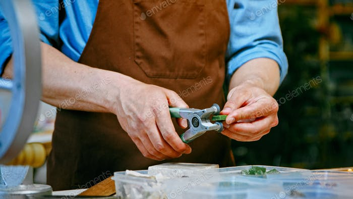 Male hands cutting a piece of stone