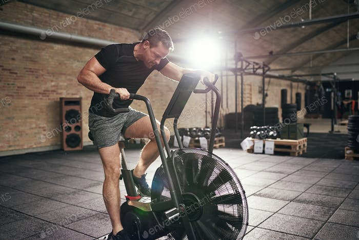 Muscular male working out on cycling machine