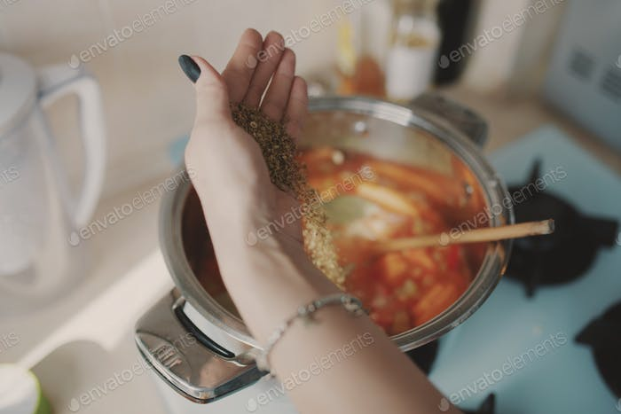 Young woman preparing pumpkin soup