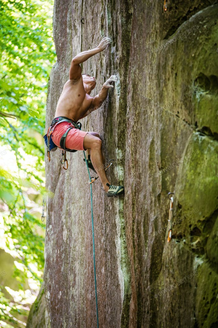 Young male rock climber on challenging route