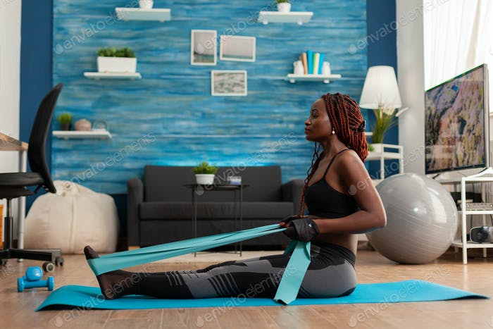 Fit strong afro woman training home living room using resistance band