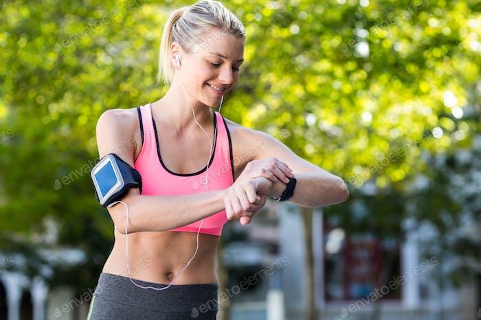 Eine schöne Sportlerin beobachtet ihre Uhr an einem sonnigen Tag
