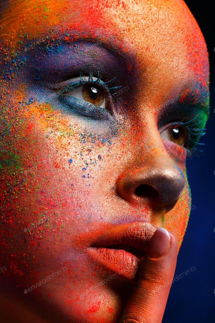Модель с художественным макияжем позирует на темном фоне