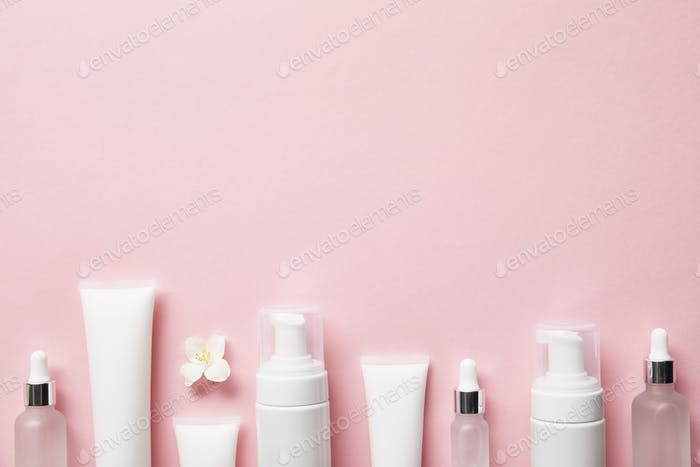 Draufsicht auf kosmetische Glasflaschen, Cremetuben mit Sahne, Kosmetikspendern und Jasminblüten