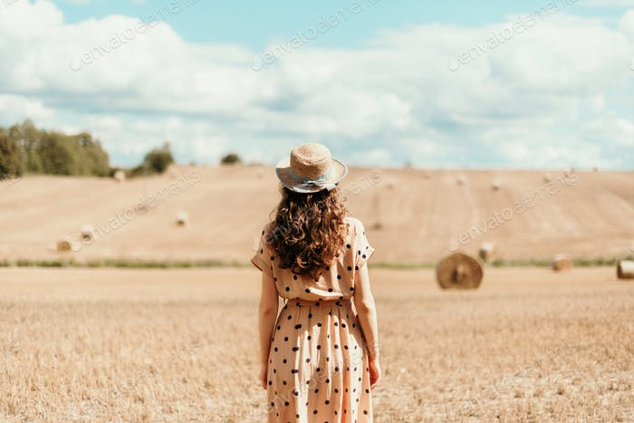 Girl in polka dot dress with curly hair, straw hat walking in field. Thanksgiving day, autumn