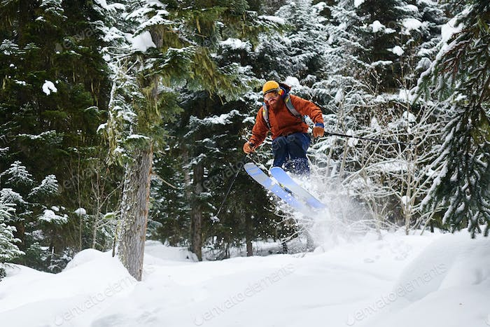 male skier jumping high in forest