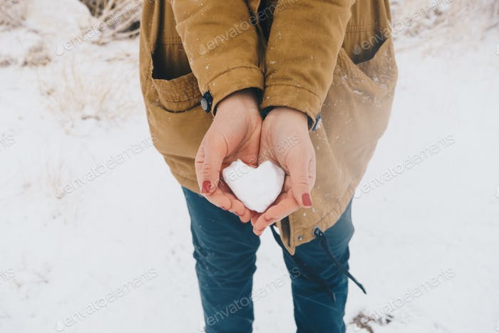 Heart from snow in female hands