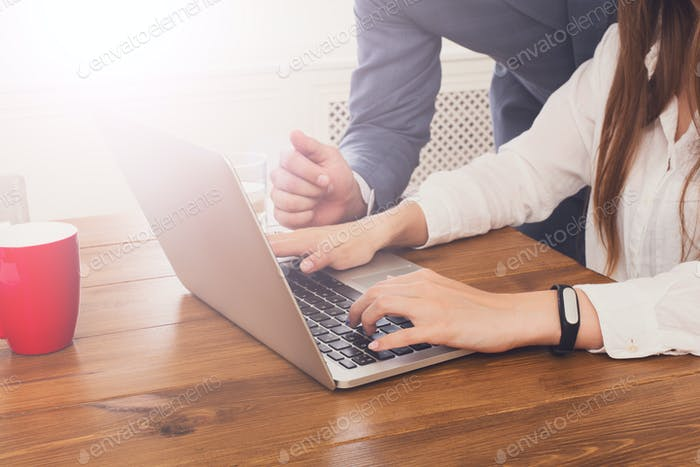 Businessman supervising secretary work on laptop, closeup of han