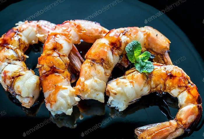 Fried shrimps with lemon wedges on the black background
