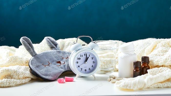 Sleeping mask, alarm clock, earplugs and pills. Healthy night sleep creative concept.