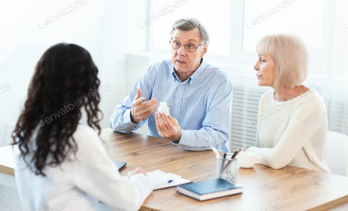 Mature couple asking doctor how to use pill