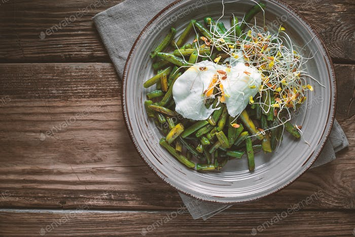 Salad with beans, sprouted flax and quail eggs on a ceramic plate