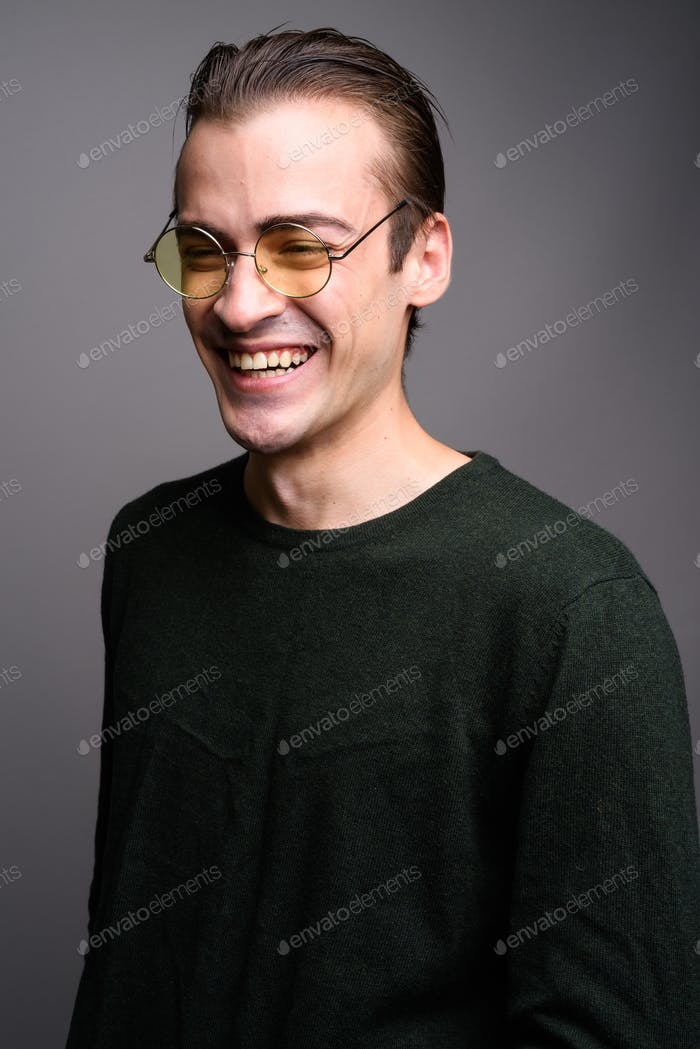 Young handsome man laughing against gray studio background
