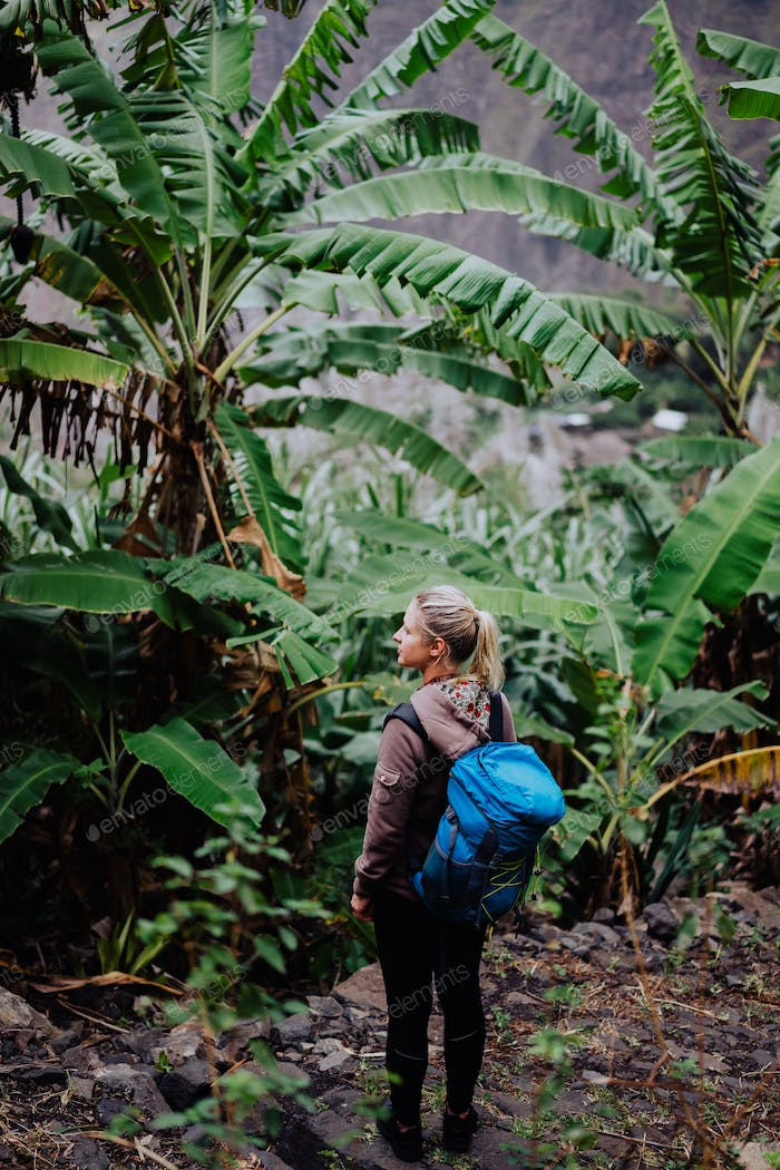 Santo antao island. Cape verde. Blond young women with blue backpack walking through banana