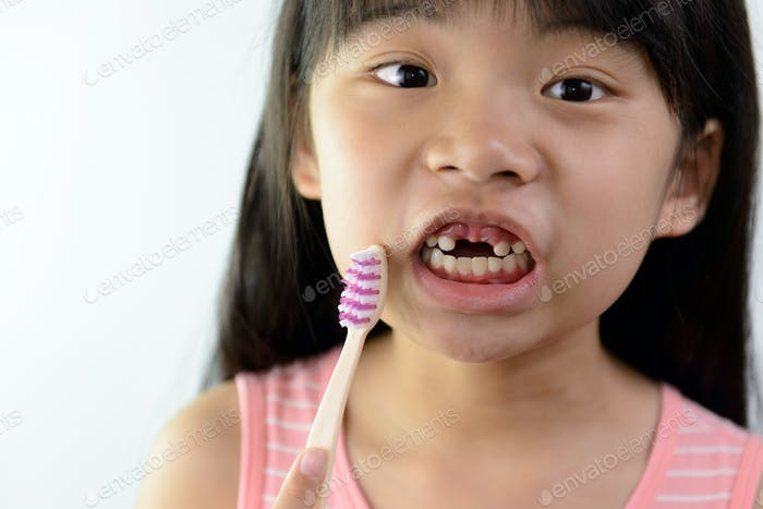 Little girl without front teeth with tooth brush