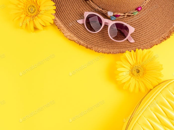 Yellow fashion holiday background with straw hat, sunglasses, handbag and flowers on monochrome