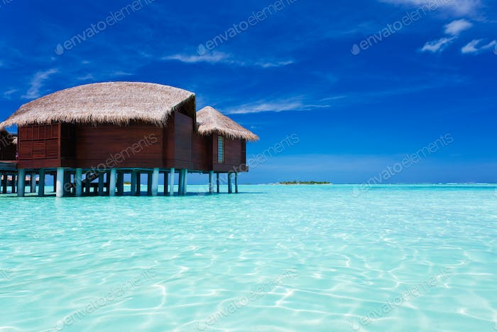 Overwater bungalow in lagoon around tropical island