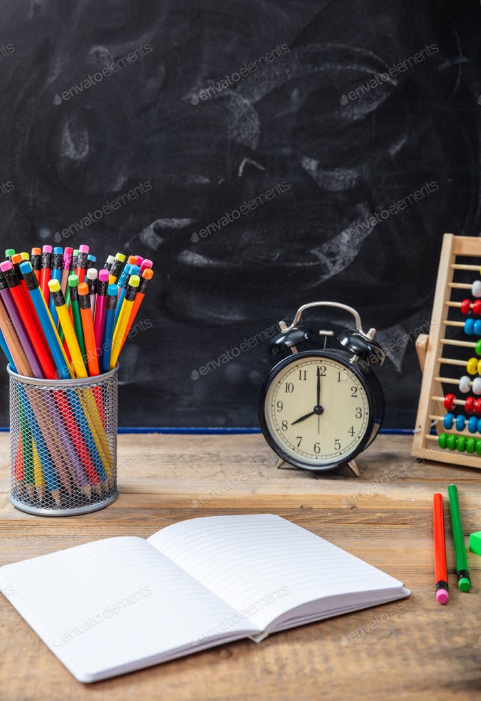 School supplies and alarm clock on wooden desk, blackboard background