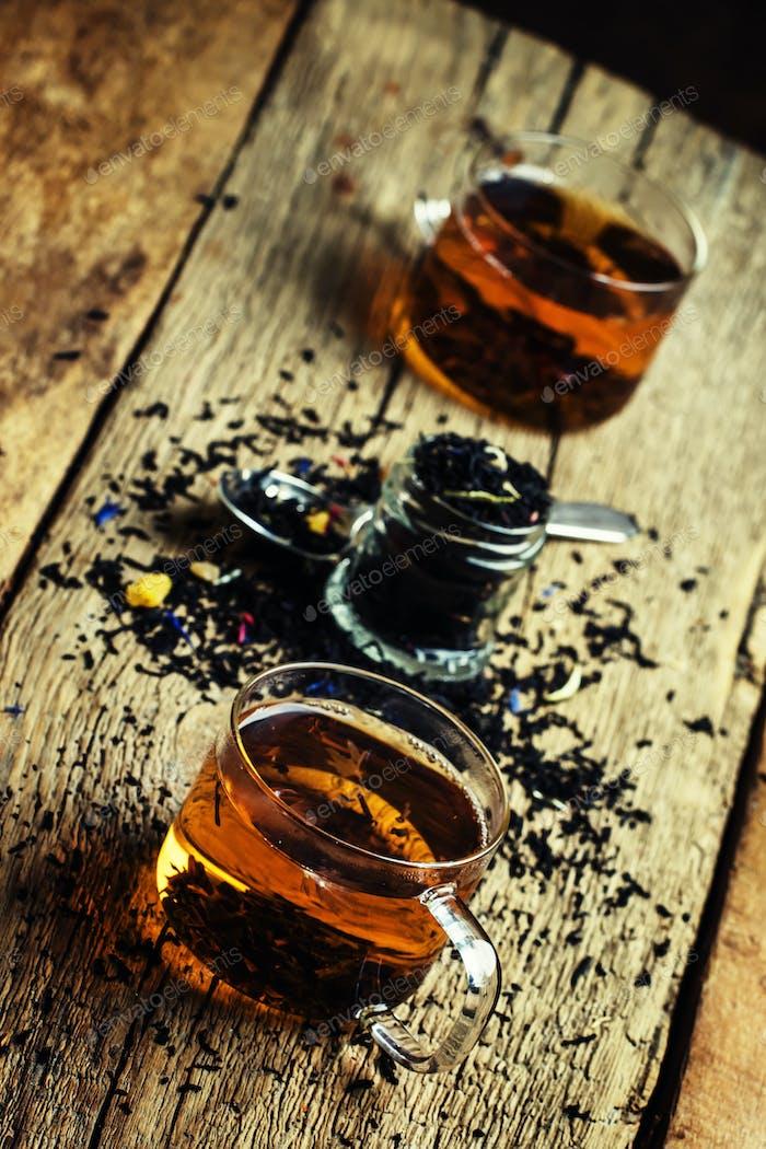 Schwarzer Tee mit Blumen Kornblume und getrockneten Früchten in Glastassen