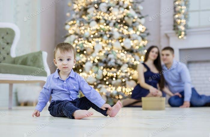 Bebê bonito sentado no chão. Os pais a vigiá-lo na árvore de Natal. Rapaz em foco.