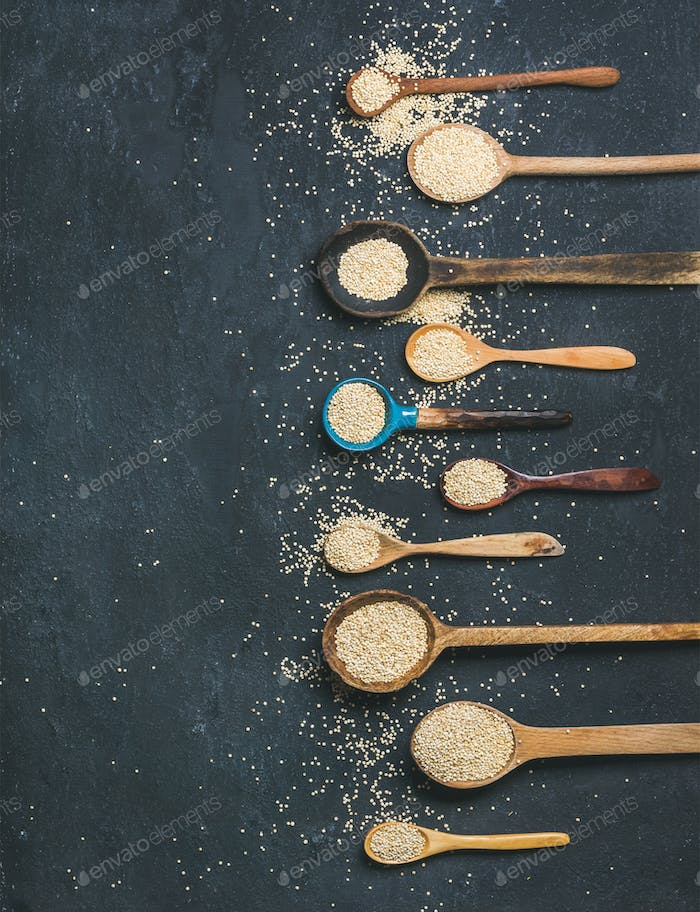 Quinoa seeds in spoons over black stone background, copy space