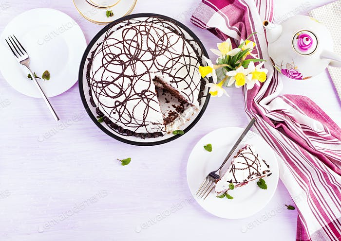 Chocolate cake with cherries and  cream on light background. Top view, overhead