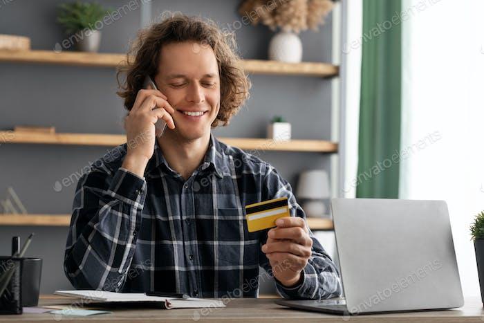 Hombre Alegre Con Tarjeta De Crédito Llamando Al Banco En La Oficina