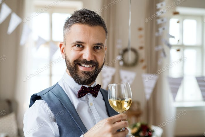 A portrait of a mature man standing indoors in a room set for a party, holding wine.