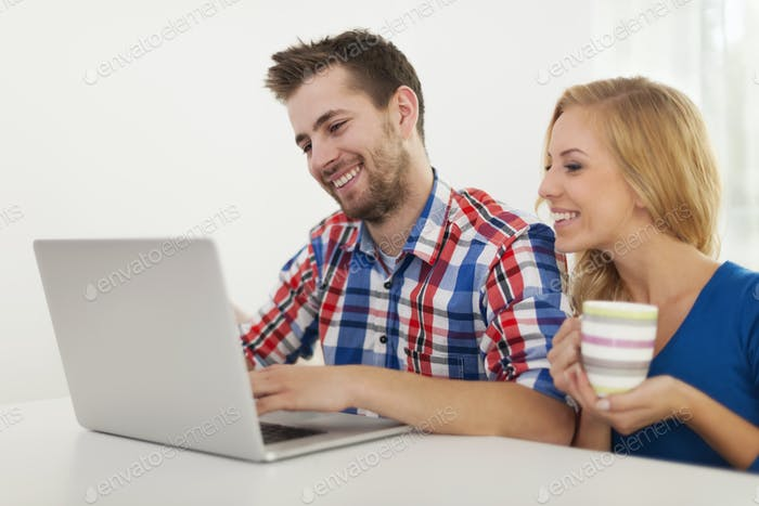 Couple checking something on computer at home