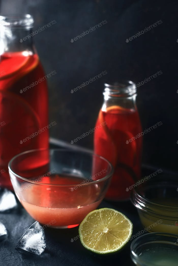 Citrus cocktail in the different glass bottle and bowl on the dark stone background