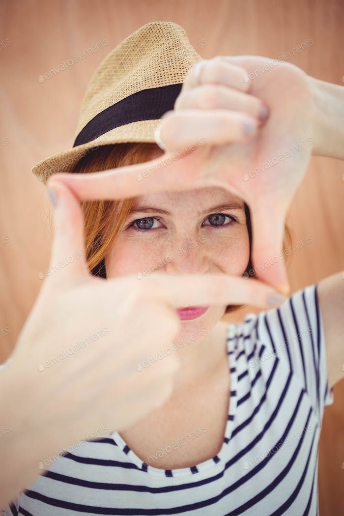 blue eyed hipster in a trilby, looking through her hands