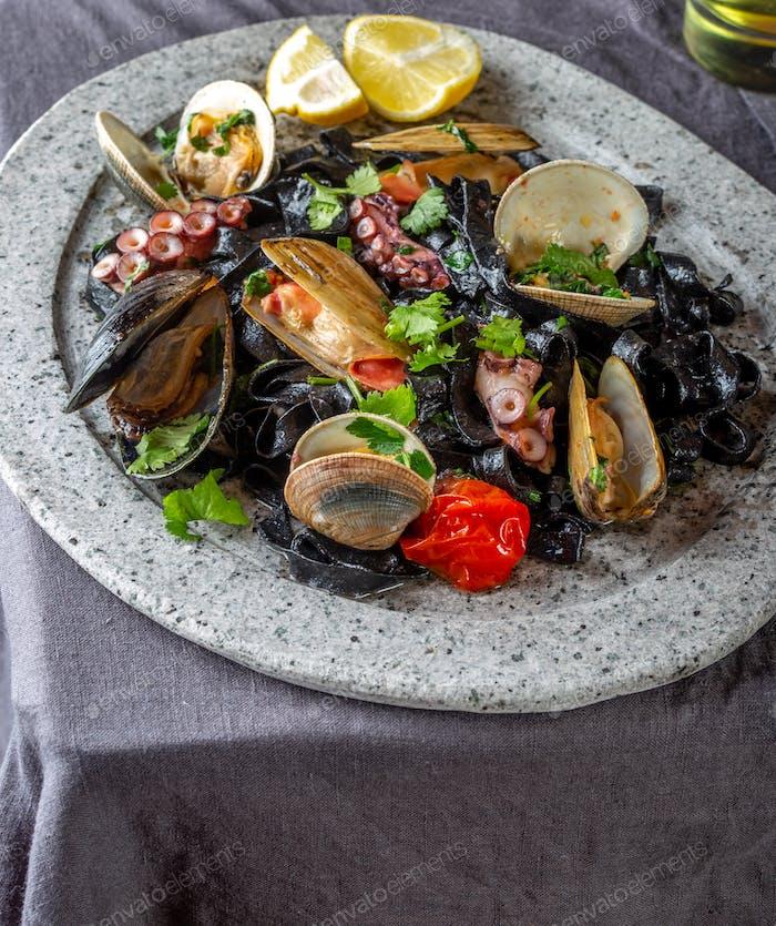 Schwarze Spaghetti mit Meeresfrüchten auf schwarzem Tisch.