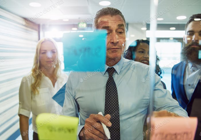 Businessman looking at sticky notes on glass