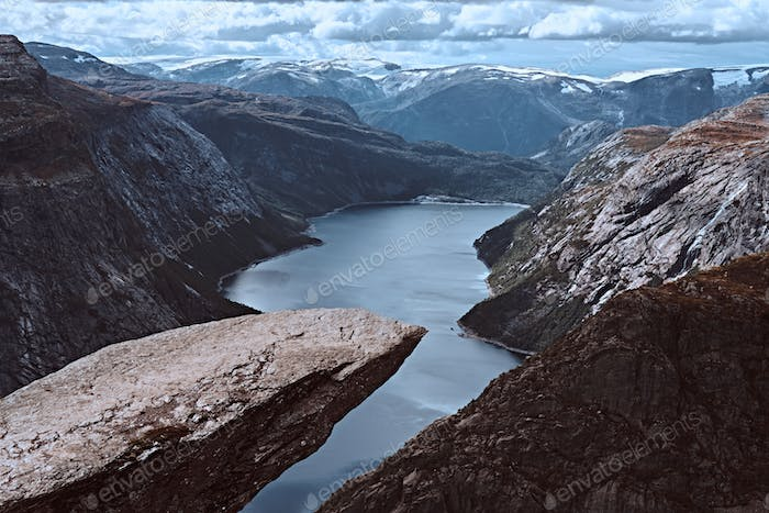Tourist man sitting in the Trolltunga and enjoys the beautiful view of the Norwegian fjord.