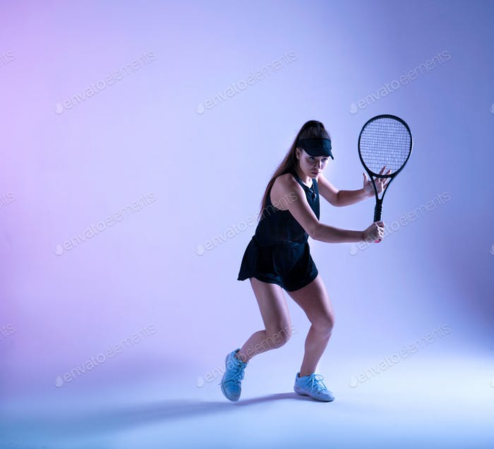 Young female tennis player preparing to hit the ball.