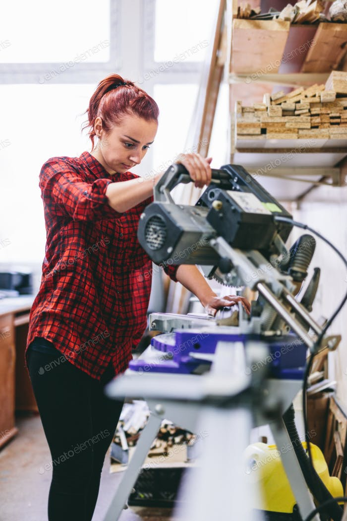 Woman manual worker operating tools in workshop